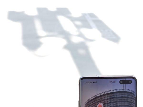 Ein 5G-Smartphone vor dem Schatten eines Funkmastes