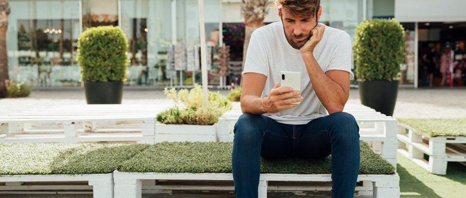 Ratlos schaut ein Mann auf sein Smartphone. Der Grund: Kein Empfang.