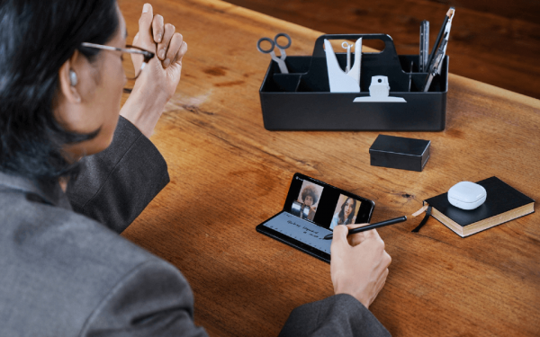 Eine Frau sitzt am Schreibtisch und notiert Ideen auf ihrem faltbaren Smartphone.