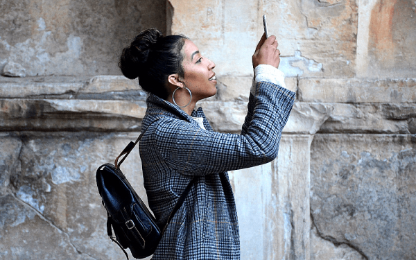 Eine Frau fotografiert mit ihrem Smartphone: Jederzeit Eindrücke teilen zu können, zählt zu den Vorzügen des Handys.