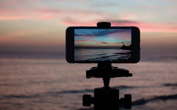 Smartphone klemmt auf einem Stativ, um den Sonnenuntergang zu fotografieren.