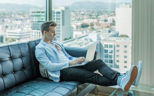 Junger Mann sitzt auf dem Sofa und surft am Laptop.