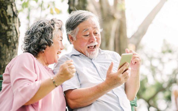 Ein älteres Paar lacht herzlich beim Blick auf das Smartphone. Vermutlich über ein lustiges Video vom Enkel ider einer Katze.