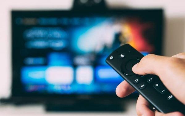 Eine Fernbedienung deutet auf ein TV-Gerät. Der Zuschauer nutzt Internetfernsehen.