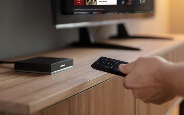 Die Fernbedienung in der Hand deutet auf die Set-Top-Box. Sie braucht der Zuschauer, um IPTV zu empfangen.