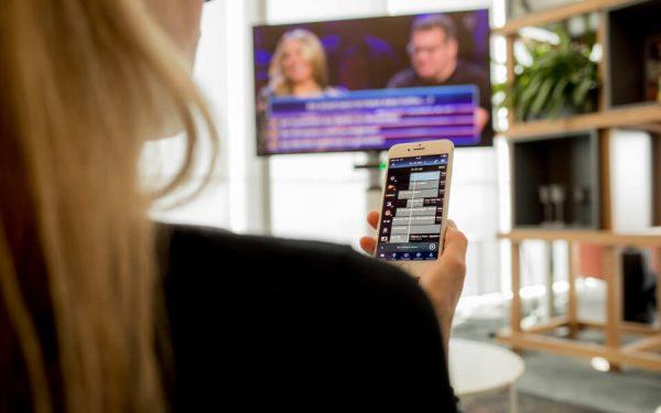 Eine TV-Zuschauerin sieht eine Quizsendung. Über das Smartphone Smartphone rätselt sie mit. IPTV macht solche Interaktion möglich.