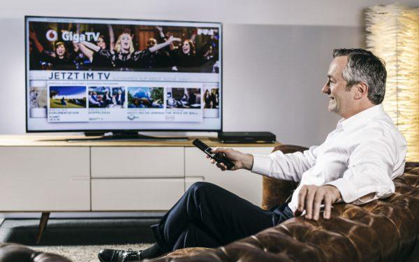 Ein Mann sitzt auf dem Sofa und verschafft sich einen Überblick, was gerade im TV-Programm läuft. Die Sender empfängt er über IPTV.