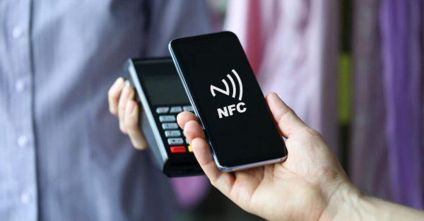 Ein Smartphone wird vor ein NFC-Lesegerät gehalten. Auf dem Display des Handys ist das Wellensymbol für die NFC-Technologie zu sehen.