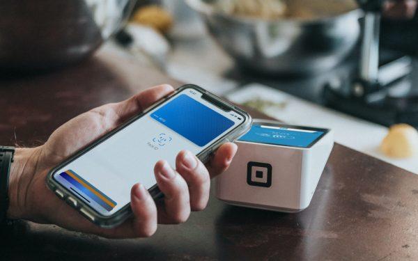 Bezahlen im Café: Jemand hält sein iPhone ans Kassenterminal und autorisiert via Face ID die Transaktion.