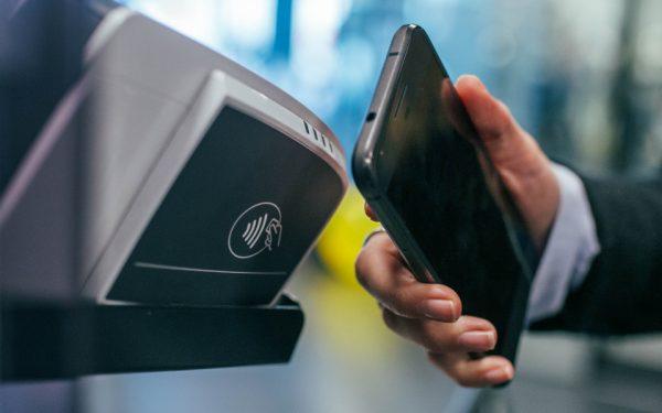 Ein Smartphone wird an ein NFC-fähiges Kassenterminal gehalten. Auf dem Lesegerät ist das Wellensymbol der Funk-Technologie zu sehen.