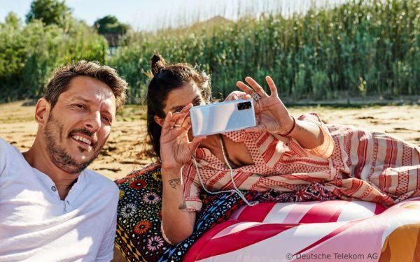 Ein Paar entspannt beim Picknick. Die Frau fotografiert mit ihrem Smartphone.