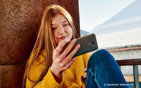 Teenagerin schaut auf ihr Smartphone-Display.